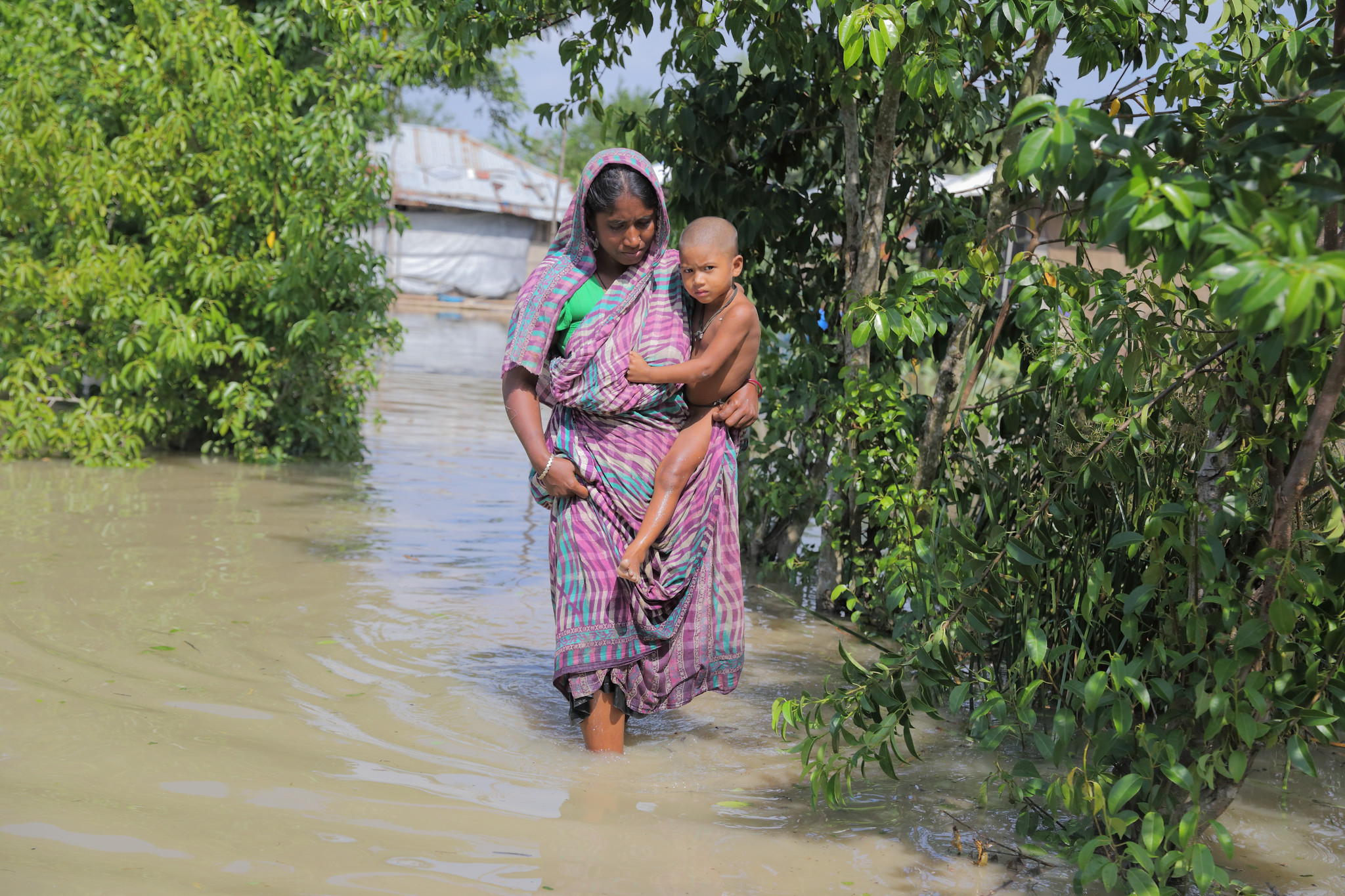 Photo of a woman crossing flood water and carrying a baby