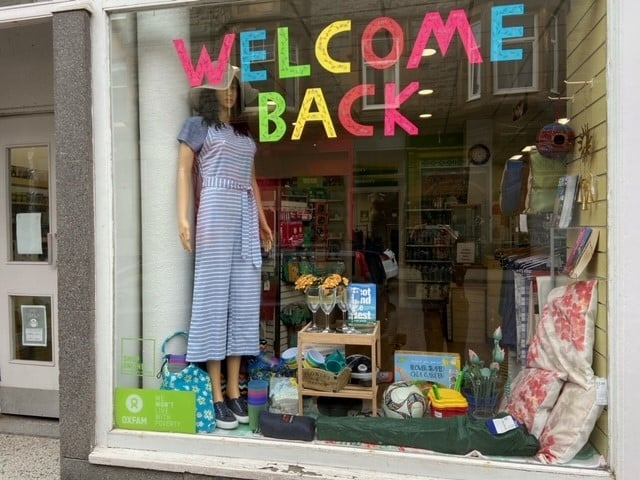 Oxfam Oban shop window with text saying welcome back
